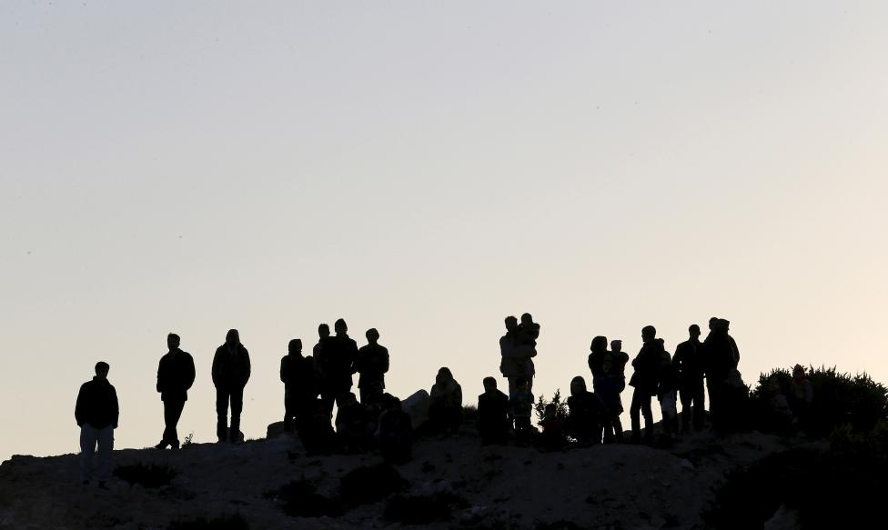 Refugees stand on top of a hill as the others try to sail off for the Greek island of Chios from the western Turkish coastal town of Cesme, in Izmir province, Turkey, November 4, 2015. REUTERS/Umit Bektas